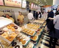 Sweet smell of success: Reporters are given a preview of a new Krispy Kreme Doughnut shop that will open Thursday in Osaka's Shinsaibashi district.   KYODO PHOTO