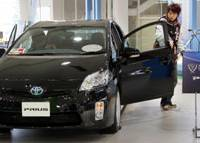 Prius look: Visitors check out a 2010 Toyota Prius hybrid at a Toyota Motor Corp. showroom in Tokyo on March 4. | AP PHOTO