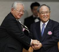 Changing of the Guard: Hiromasa Yonekura (left), the new chairman of the Japan Business Federation (Nippon Keidanren), shares a moment with departing Chairman Fujio Mitarai during a general meeting in Tokyo on Thursday. | AP PHOTO