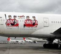 Flying billboard: A Boeing 777 sporting the images of Fukuoka Softbank Hawks players sits on the apron at Haneda airport Wednesday. Japan Airlines Corp. has started flying the jet between Tokyo and Fukuoka in collaboration with Softbank Corp.   KYODO PHOTO