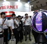 Eyes on the prize: Visitors using special glasses try out Panorama Ball Vision, which projects three-dimensional, 360-degree images, at NAC Image Technology Inc.'s booth Thursday during the 3D & Virtual Reality Expo at Tokyo Big Sight. | KAZUAKI NAGATA PHOTO