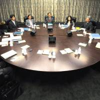 Bank on it: Bank of Japan Gov. Masaaki Shirakawa (center) sits with his Policy Board members at the start of their April meeting. | BLOOMBERG PHOTO