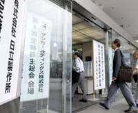All on one day: Shareholders enter a building in Nakano Ward, Tokyo, where Hitachi Ltd. and other firms held meetings with investors Tuesday. | KYODO PHOTO