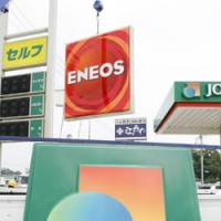 High-octane competition: A JOMO sign representing Japan Energy Corp. is taken off for replacement by an ENEOS sign from Nippon Oil Corp. at a gas station in Saitama Thursday. The two companies have merged and integrated their gas station brands. | KYODO PHOTO