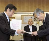 Without delay: Internal Affairs and Communications Minister Kazuhiro Haraguchi (left) demands a written explanation Tuesday from Japan Post Service Co. President Shinichi Nabekura about delays in parcel deliveries.   KYODO PHOTO