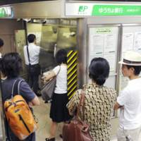 Bank holdup: Customers wait while Japan Post Bank ATMs are being fixed in Minato Ward, Tokyo, on Monday. | KYODO PHOTO