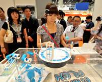 A woman wearing a 'brain wave' headset tests Sega's Mindflex game to move a ball levitated by a circular fan through hoops, on the first day of Tokyo International Toy Show 2010 Thursday. | YOSHIAKI MIURA PHOTO