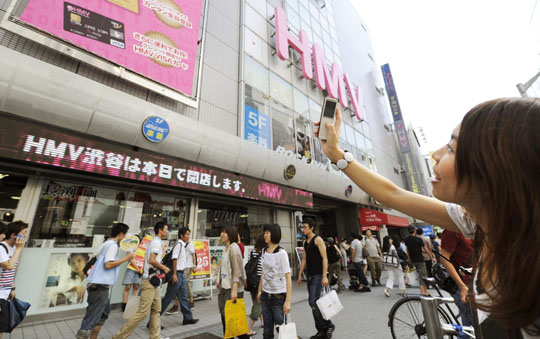 For the memory: A woman takes pictures of HMV flagship outlet in Tokyo's trendy Shibuya area on Sunday with her cell phone. The flagship music store closed for good later in the day.   KYODO PHOTO