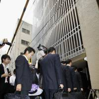 Taking over: Officials from Deposit Insurance Corporation of Japan, which will manage Incubator Bank's operations and assets during its bankruptcy proceedings, enter the bank's head office in Chiyoda Ward, Tokyo, on Friday.   KYODO PHOTO