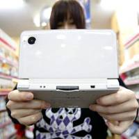 Sagging sales: A woman tries out Nintendo's DSi LL hand-held console at a game store in Soka, Saitama Prefecture, in March.   BLOOMBERG PHOTO