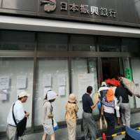 Cash back: Depositors enter the head branch of the failed Incubator Bank of Japan in Chiyoda Ward, Tokyo, on Monday to get refunds.   KYODO PHOTO
