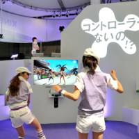 Two women play a beach volleyball video game on Microsoft's Xbox 360 console with the new Kinect camera-sensor system at the Tokyo Game Show at Makuhari Messe hall in Chiba on Thursday.   YOSHIAKI MIURA PHOTO