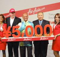 Low-cost carrier: Azran Osman-Rani (center), CEO of AirAsia X, and Dato' Shaharuddin bin Md Som (second from right), the Malaysian ambassador to Japan, announce Tuesday in Tokyo that AirAsia X will be offering special 5,000 yen tickets for one-way Tokyo-Kuala Lumpur flights for a limited time. | KAZUAKI NAGATA