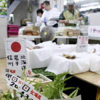 For big spenders: Boxes of 'matsutake' mushrooms, the nearest with three from Iwate Prefecture and priced at 90,000 yen, are on sale at a wholesale shop in Tokyo's Tsukiji market Friday.   KYODO PHOTO