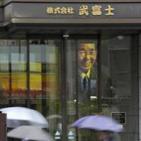 Troubled lender: Pedestrians walk past Takefuji Corp. headquarters in Shinjuku Ward, Tokyo, on Monday. A photo of the company's late founder, Yasuo Takei, is displayed inside the building. | KYODO PHOTO