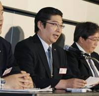 Picking up the pieces: Takefuji Corp.'s new president, Junichi Yoshida (center), announces Tuesday at the Tokyo Stock Exchange the consumer lender has filed for bankruptcy. | KYODO PHOTO