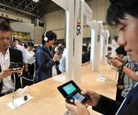 Game on: Invited guests try Nintendo's new 3DS handheld at Makuhari Messe in Chiba Prefecture on Wednesday. The 3-D console will hit the market in February. | YOSHIAKI MIURA PHOTO