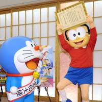 High-level post: Cartoon character Doraemon (left), who was appointed Japan's first 'anime ambassador' in March 2009, celebrates the appointment with his friend, Nobita, at the Foreign Ministry the same month. | KYODO PHOTO