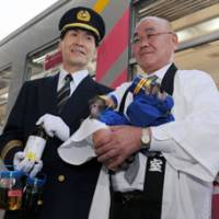 Beyond steam: In railway garb, Mayor Chozo Nakagawa of Kasai, Hyogo Prefecture, holds bottles of biodiesel for a train Saturday at the city's Hojomachi Station, in the presence of two baby monkey 'stationmasters.' | KYODO PHOTO