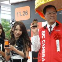 Raising the smart phone bar: KDDI Corp. Senior Vice President Takashi Tanaka pitches the new IS03 smart phone with members of the idol group SDN48 Friday at the Bic Camera electronics outlet in Tokyo's Yurakucho district. | KAZUAKI NAGATA PHOTO