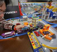 Playmaker: Tomy Co. executive Hisanao Takahashi sets up the toy maker's Tomica Mega Station Set at its headquarters in Tokyo on Tuesday. | AP PHOTO