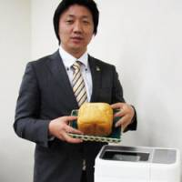 Rolling in dough: Masanori Okamoto, a product planning manager for Sanyo Consumer Electronics Co., shows off a loaf of bread made with rice in the firm's Gopan bread cooker during an interview in Tokyo on Dec. 13. | KYODO PHOTO