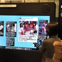 Vital signs: Visitors look at a digital sign in the Daimaru department store at Tokyo Station this month. The sign enables store tenants to disseminate up-to-date information about their goods and services. | YOSHIAKI MIURA PHOTO