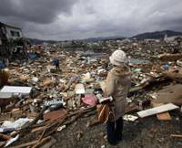 Taking stock: A woman looks at debris from the March 11 quake and tsunami in Kasennuma, Miyagi Prefecture, on Tuesday. | BLOOMBERG