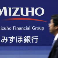 On the move: A pedestrian walks past the logo for Mizuho Bank Ltd. in Tokyo in May. | BLOOMBERG PHOTO