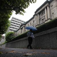 Stormy weather: A man passes the Bank of Japan headquarters in Tokyo on Aug. 22.   BLOOMBERG PHOTO