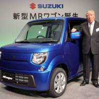 Fork in the road: Suzuki Motor Corp. Chairman Osamu Suzuki poses with the new MR Wagon minivehicle at its launch in Tokyo on Jan. 20. | BLOOMBERG
