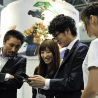 Test drive: Visitors try out new game software at the Nintendo 3DS Conference 2011 in Tokyo last week. | BLOOMBERG