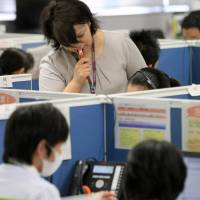 Dialing in: Tokyo Electric Power Co. employees handle telephone calls at its Fukushima Nuclear Compensation Office in Tokyo earlier this month. | BLOOMBERG