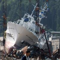 High and dry: A man on July 13 stands in front of a fishing vessel swept inland by the March tsunami in Kesennuma, Miyagi Prefecture. | BLOOMBERG