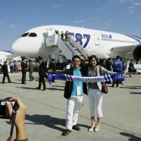 First to fly: Passengers on All Nippon Airway's Flight 7871 to Hong Kong, the first using the brand new Boeing 787 Dreamliner, take a photo on the tarmac at Narita International Airport Wednesday morning before its departure. | KYODO