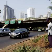 Poised for a boom: A worker sweeps the roadside along a Jakarta thoroughfare Aug. 2.   BLOOMBERG PHOTO