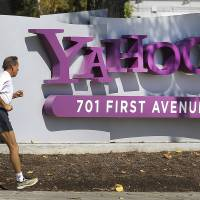 Acquisition target: A jogger passes a sign outside Yahoo! Inc.'s headquarters in Sunnyvale, California, on Oct. 13. | BLOOMBERG PHOTO