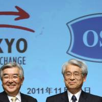 Evolving strategy: Atsushi Saito, president and chief executive officer of the Tokyo Stock Exchange Group Inc. (left), poses with Michio Yoneda, president of Osaka Securities Exchange Co., at a news conference in Tokyo on Nov. 22.   BLOOMBERG PHOTO
