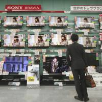 In the market: A customer looks at televisions made by Sony Corp. at an electronics store in Tokyo last month. | BLOOMBERG PHOTO