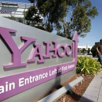 Cyberdealing: Pedestrians walk past a Yahoo Inc. sign displayed outside of the Internet company's headquarters in Sunnyvale, California, in October.   BLOOMBERG PHOTO