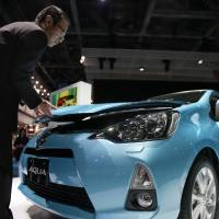 Kicking the tires: A man looks at a Toyota Motor Corp. Aqua at the Tokyo Motor Show on Nov. 30. The new hybrid vehicle went on sale on Monday.   BLOOMBERG PHOTO