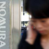 Mergers and acquisitions champ: A woman walks past a sign for a Nomura Securities Co. branch in Tokyo on Nov. 1. | BLOOMBERG PHOTO