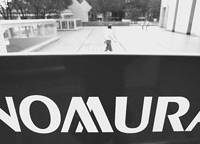 Lehman drag: A man walks behind a sign for a Nomura Securities branch in Tokyo on Nov. 1. | BLOOMBERG