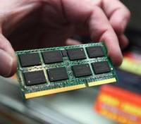 Off the old block: A sales clerk shows Elpida memory chips at an electronics shop in Tokyo in 2009. | BLOOMBERG