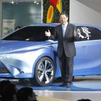 Next concept: Toyota Motor Corp. President Akio Toyoda unveils the prototype of a new hybrid car at the Auto China 2012 show in Beijing on Monday. | KYODO