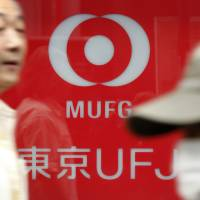 Street level: A man passes a Bank of Tokyo Mitsubishi UFJ sign in Tokyo in November. | BLOOMBERG