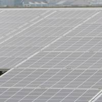 On sunny days: A worker walks near solar panels at Kyocera Corp.'s Ogishima power plant, operated by Tokyo Electric Power Co., in Kawasaki in December. | BLOOMBERG