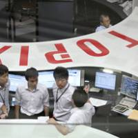 Bourse breakdown: Employees work Tuesday on the trading floor of the Tokyo Stock Exchange, where a fresh computer problem halted trading for more than 90 minutes. | BLOOMBERG