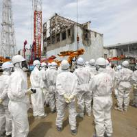Hot spot: Reporters and Tokyo Electric Power staff view the blown-out building for reactor 4 at Tepco's Fukushima No. 1 power plant near Okuma, Fukushima Prefecture, on May 26. | BLOOMBERG