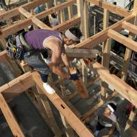 Balancing act: Carpenters work on a new home at a construction site in Yokohama in July. | BLOOMBERG